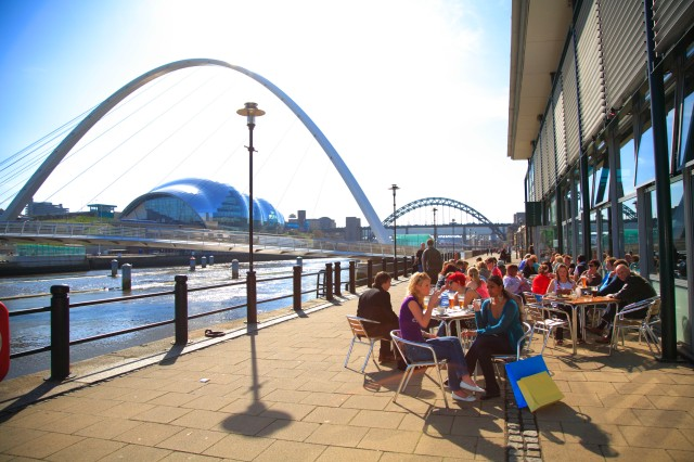 People enjoying food and drink sitting outside at the Pitcher & Piano bar on the Quayside in Newcastle. The Tyne Bridge, The Gateshead Millennium Bridge and the Sage Gateshead can be seen in the background, iconic structures representing the past and present.